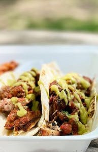 Chicken tacos with green sauce in a styrofoam container with out of focus green grass in the background beyond the table