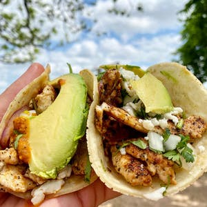 a close up of taco with marinated grilled chicken taco with onion, cilantro, queso fresco, and our signature slice of avocado on a homemade corn tortilla.