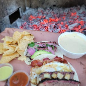 a close up of a plate of tacos and chips with sauce and queso in front of a coal fire