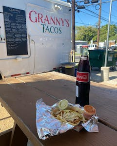 Tacos with sauce in a foil wrap with glass bottle coke on a picnic table in front of Grannys Taco truck