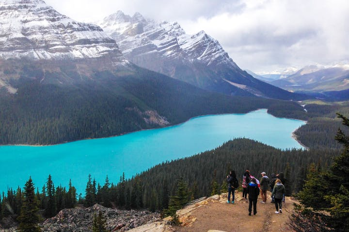 a group overlooking the lake at the base of the rockies in canada