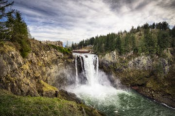 a large waterfall over a body of water with Snoqualmie Falls in the background