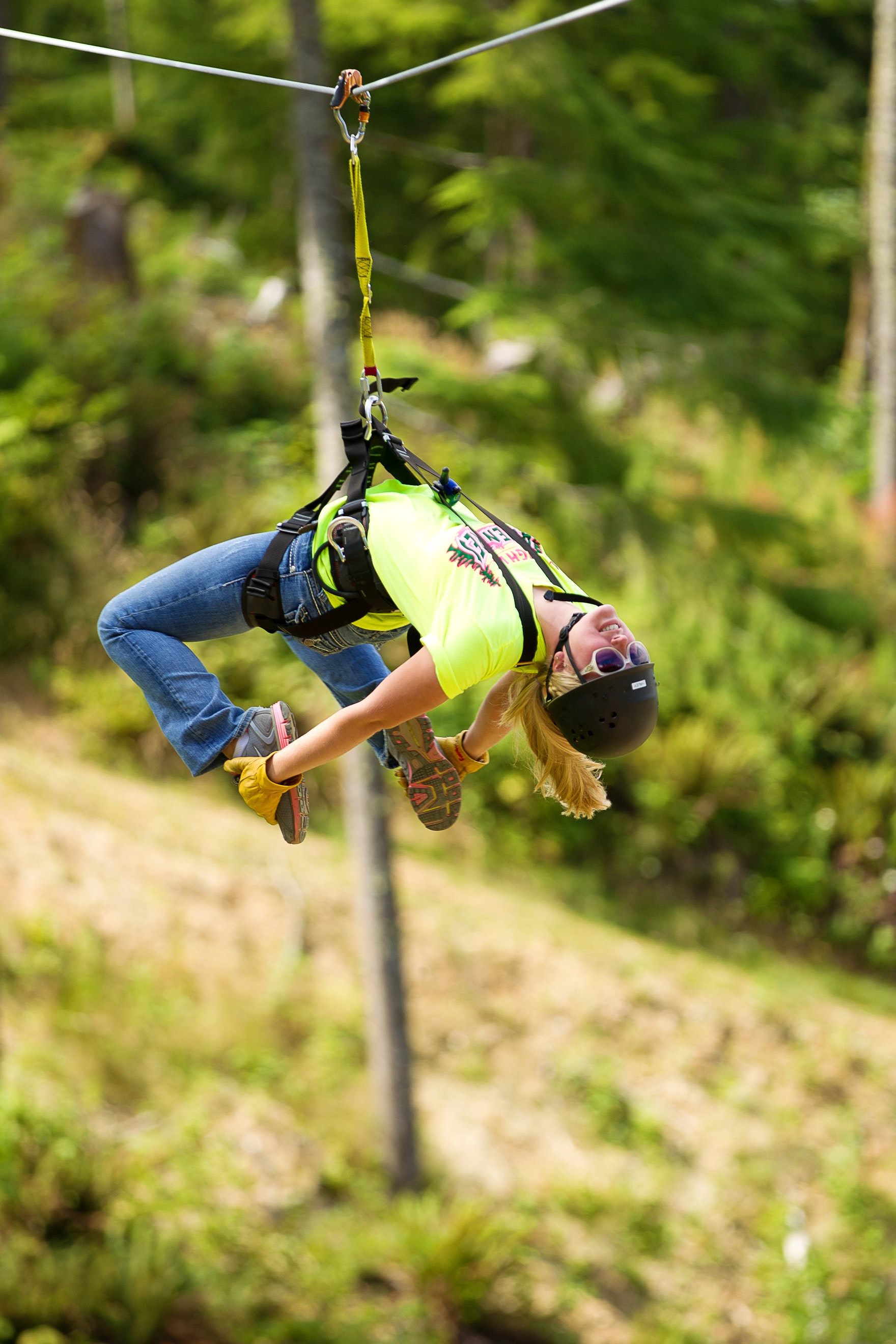 Haley grabs her feet as she zip lines