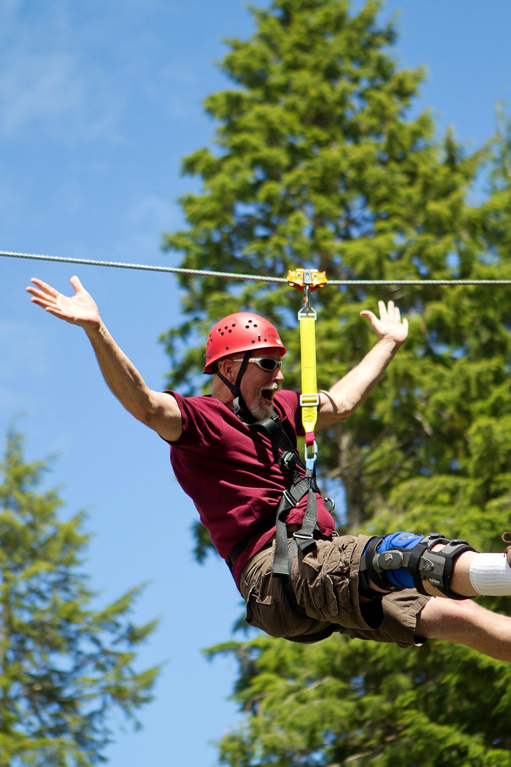 A man cheering as he rides the zipline