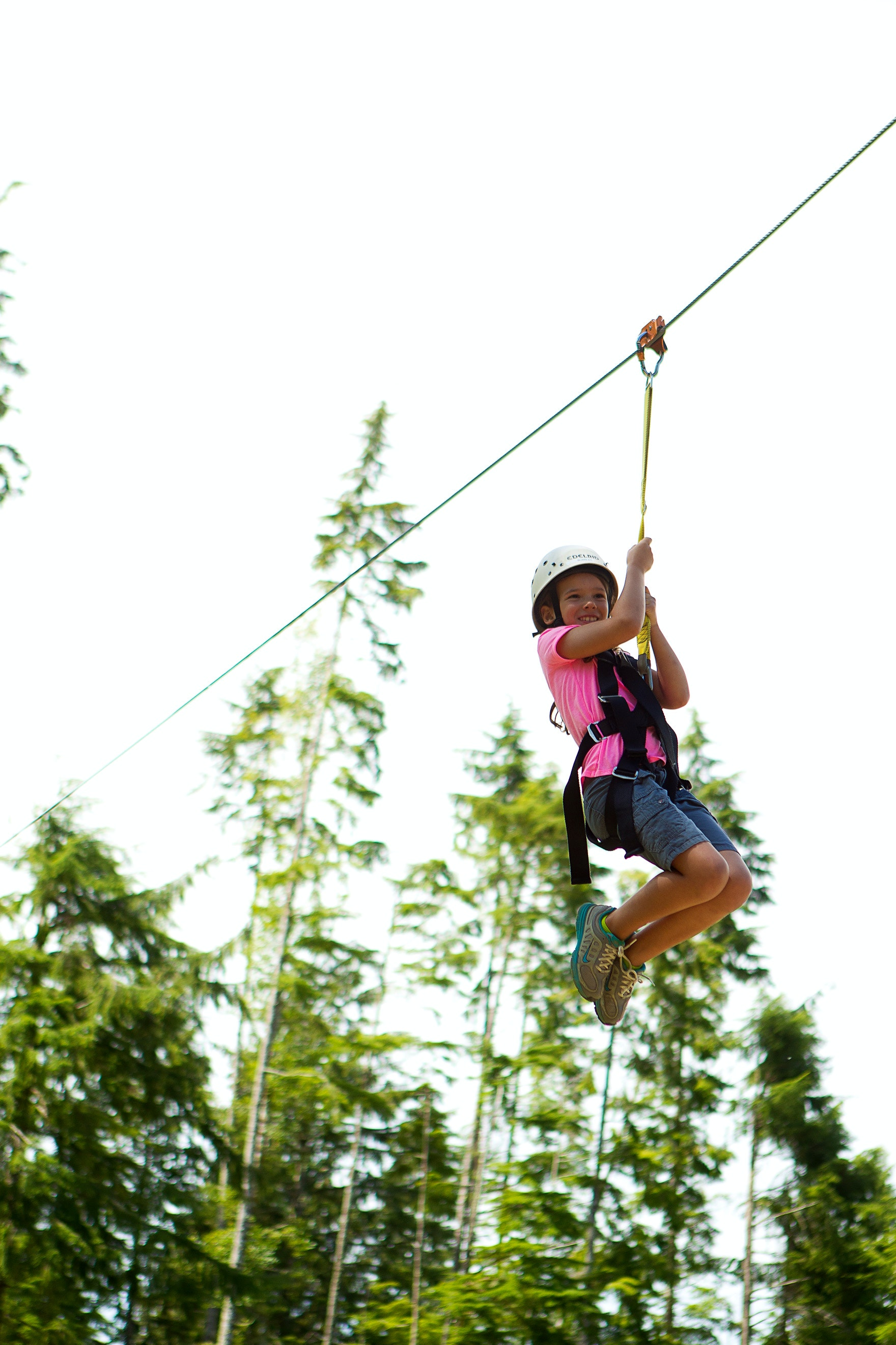 A girl zip lining over the treetops