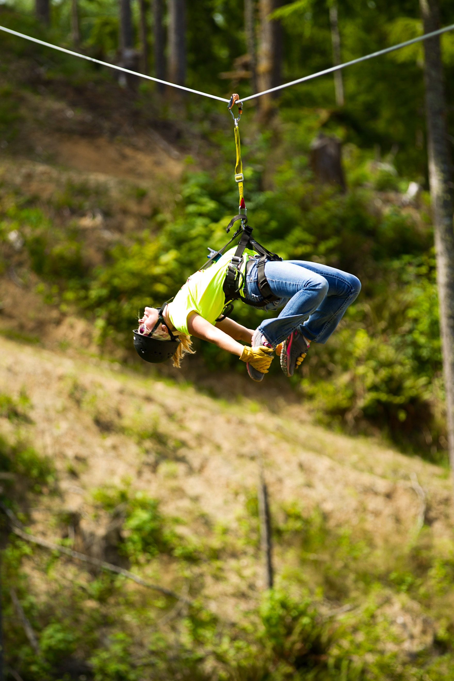 A woman grabs her feet as she zip-lines