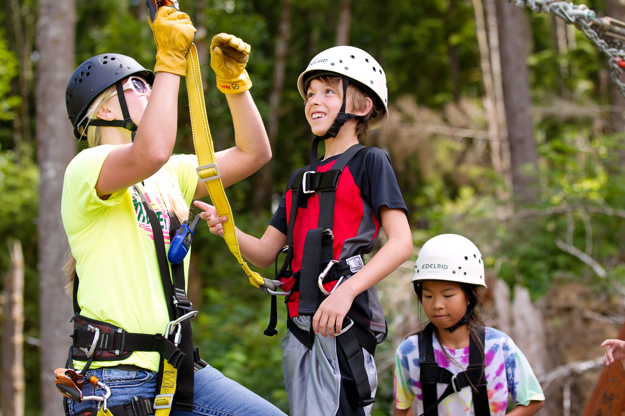 A guide helps a boy zip-line with High Life Adventures