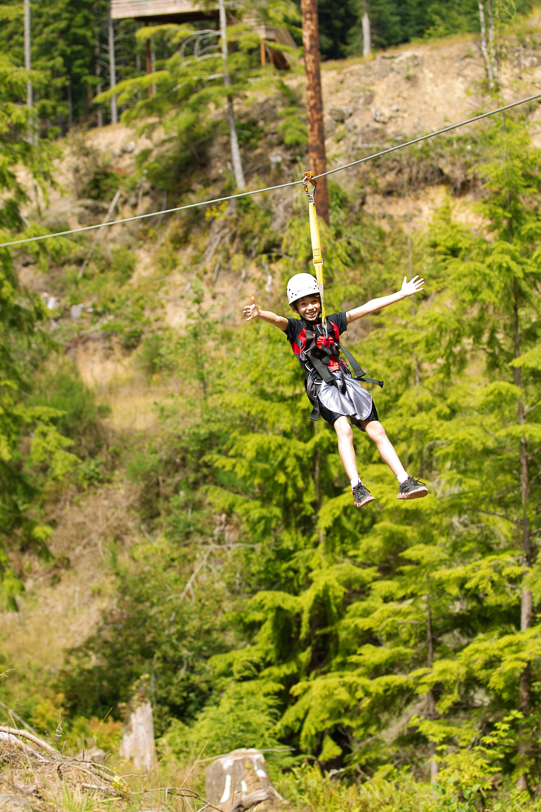 A boy ziplines with her arms outstretched