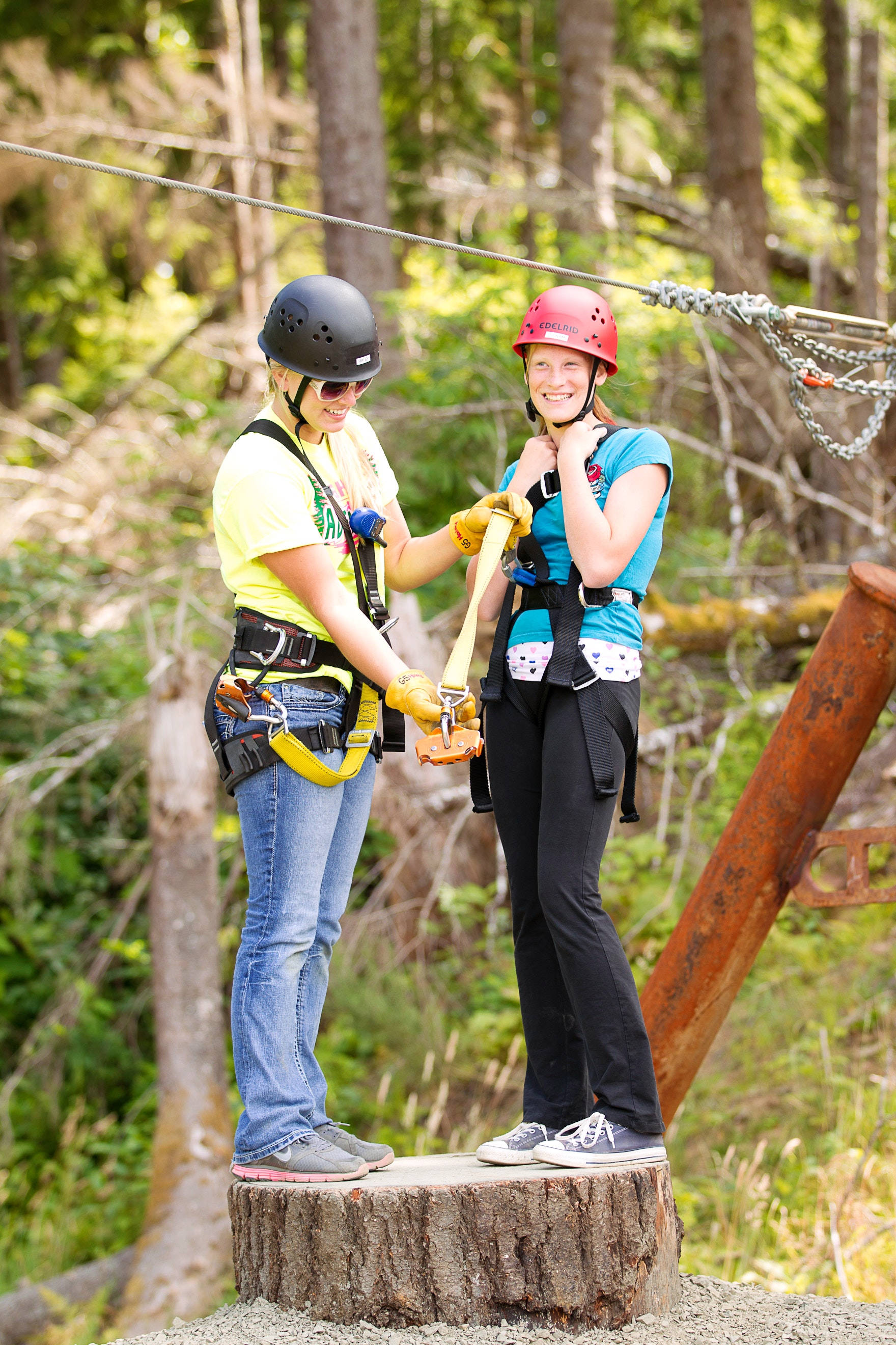 A guide helps a girl get ready to zip-line