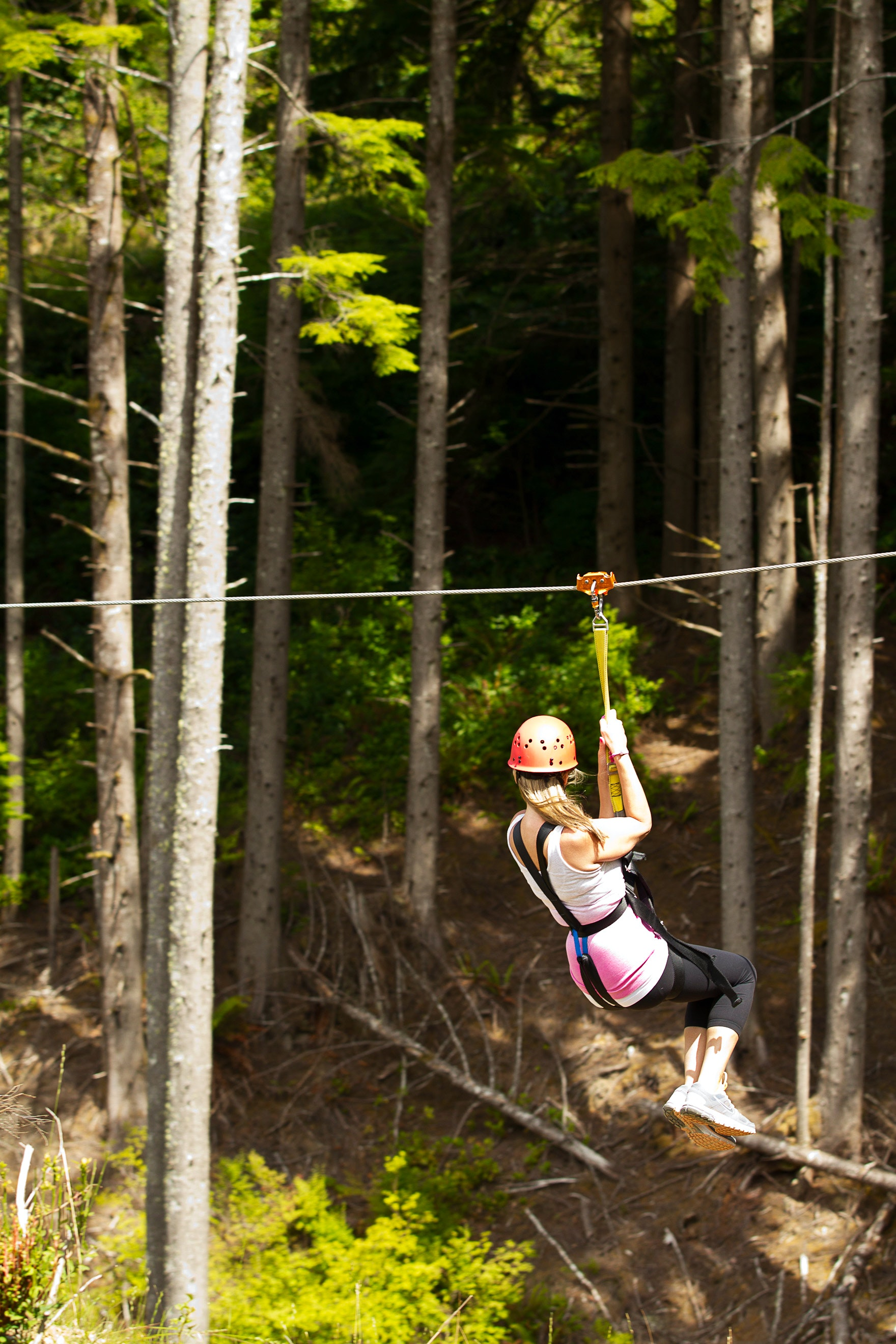 A woman ziplining through the forest in Oregon