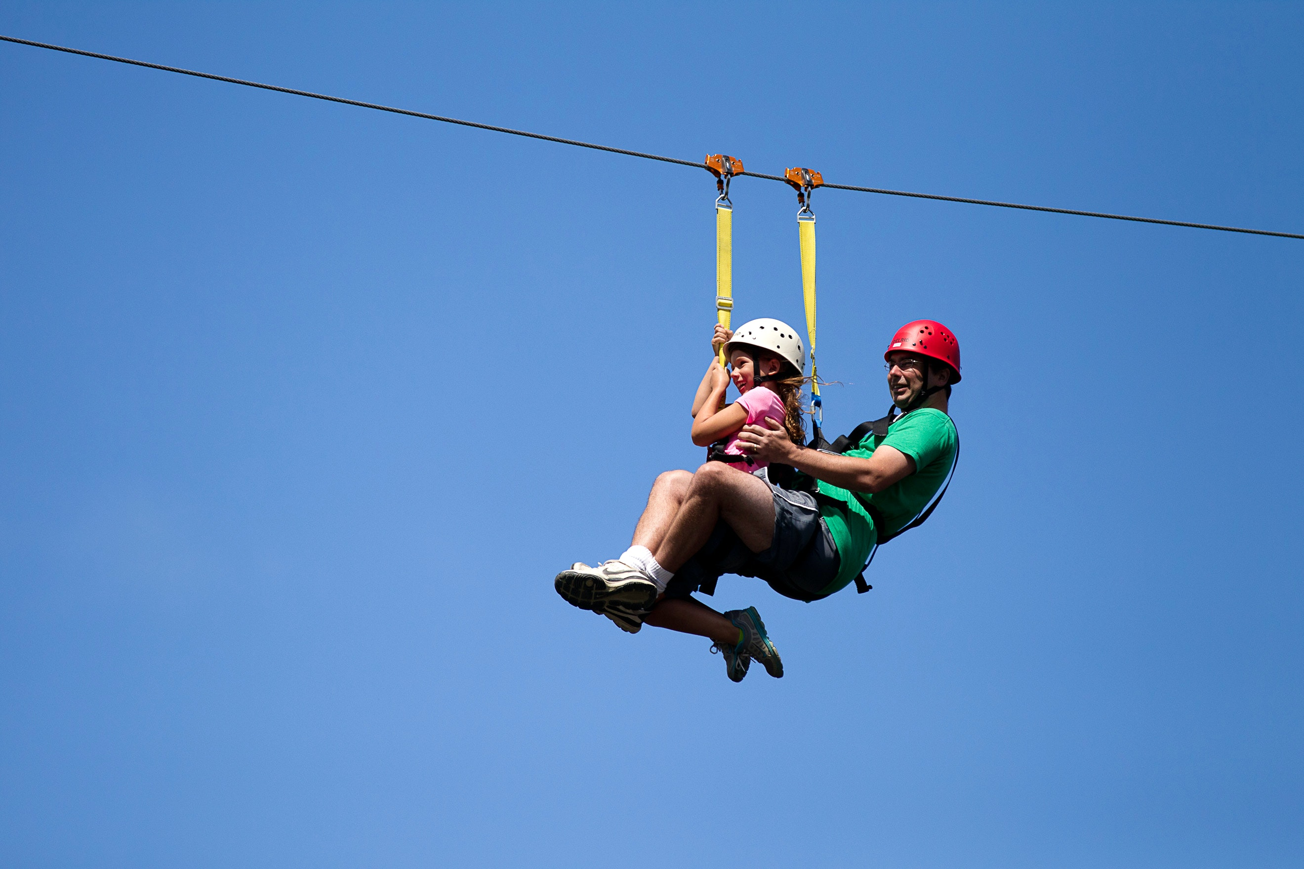 A man and girl ziplining on a sunny day