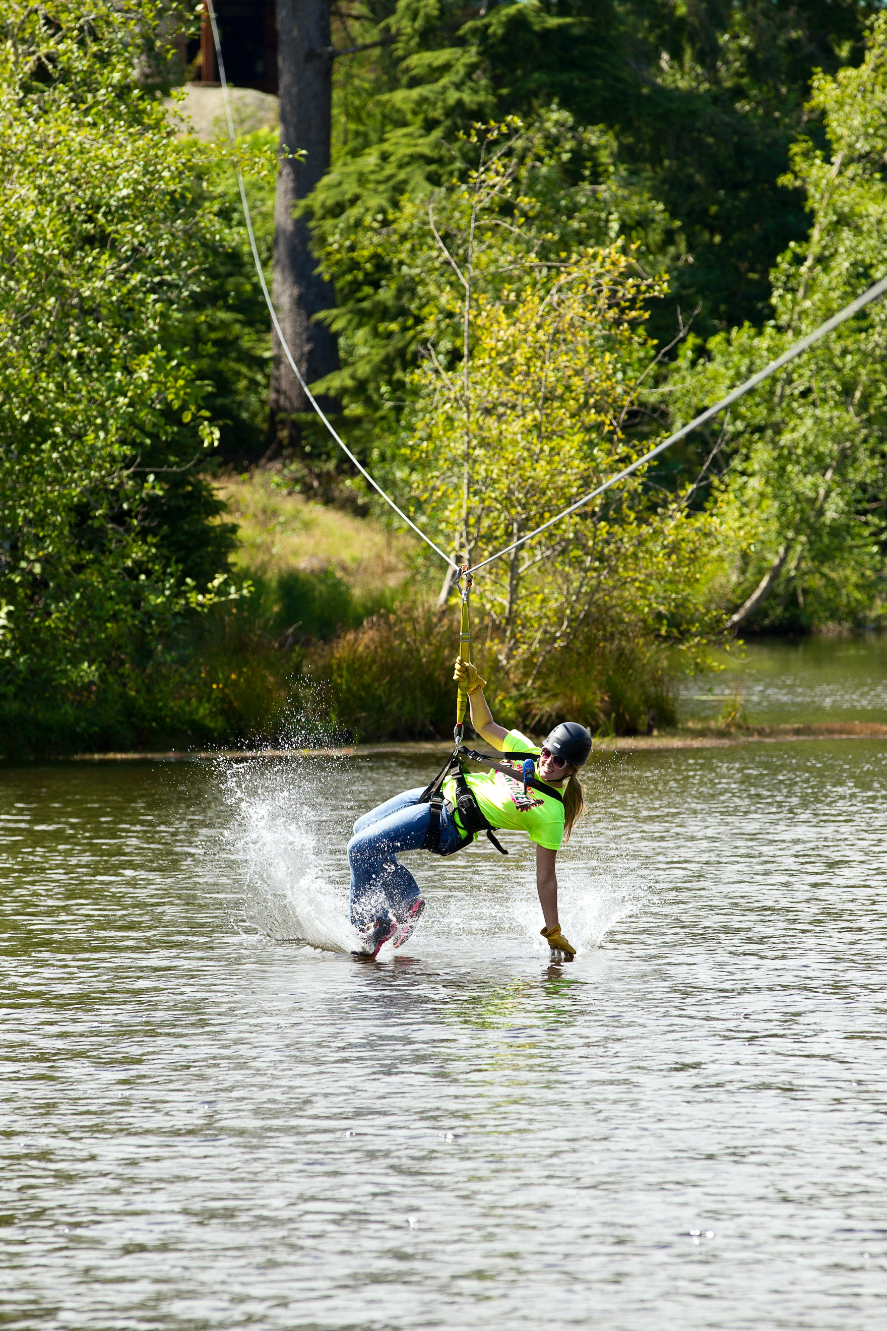 A woman skims over the water on the zipline
