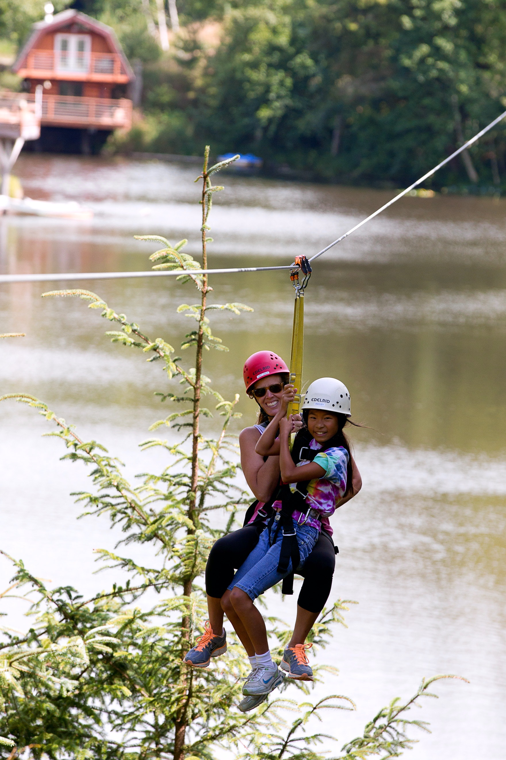 A woman and girl zipline together with High Life Adventures