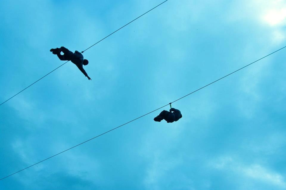 Two people ride the Spruce and Willow ziplines