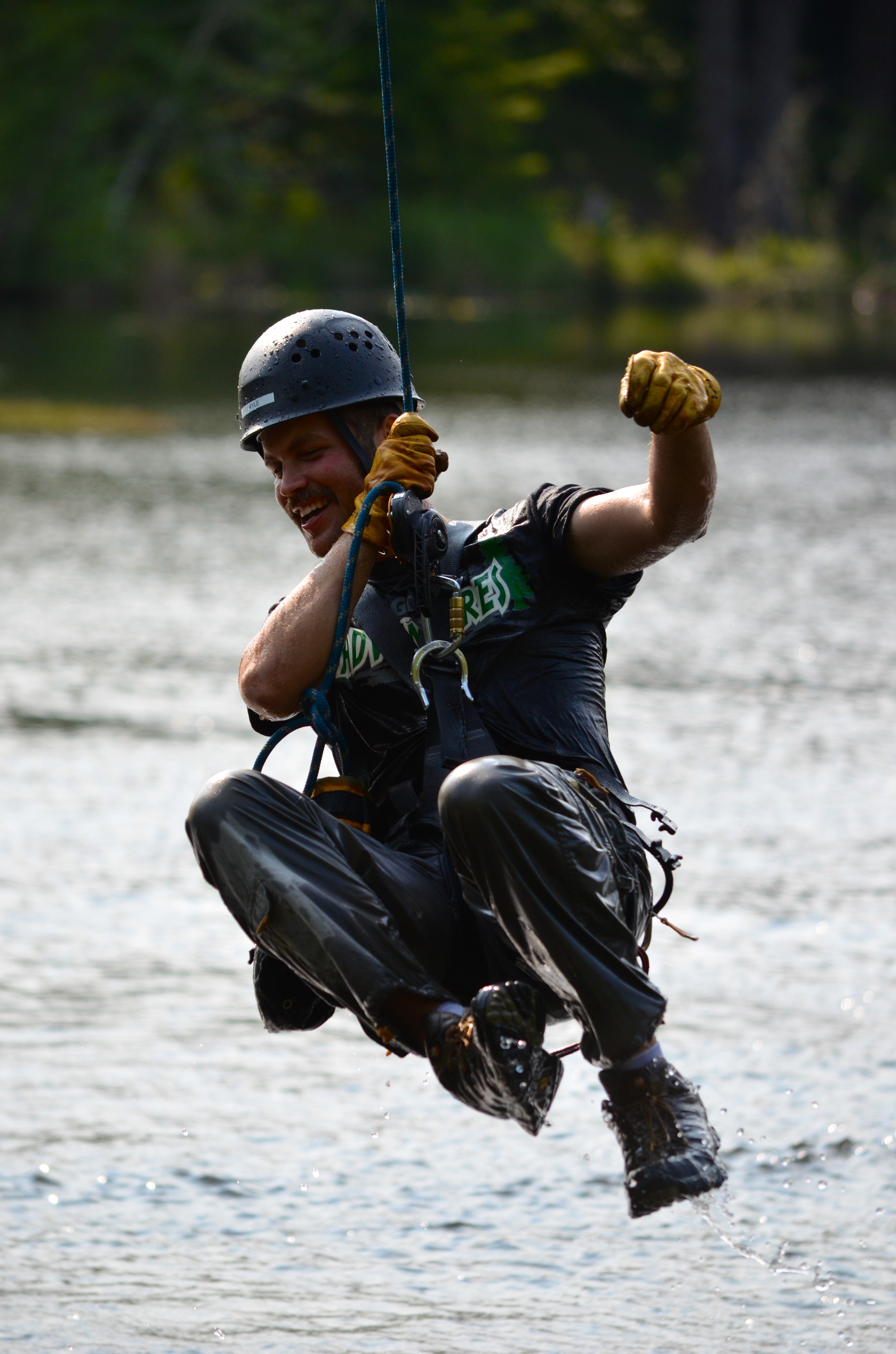 A man ziplines near the water with High Life Adventures