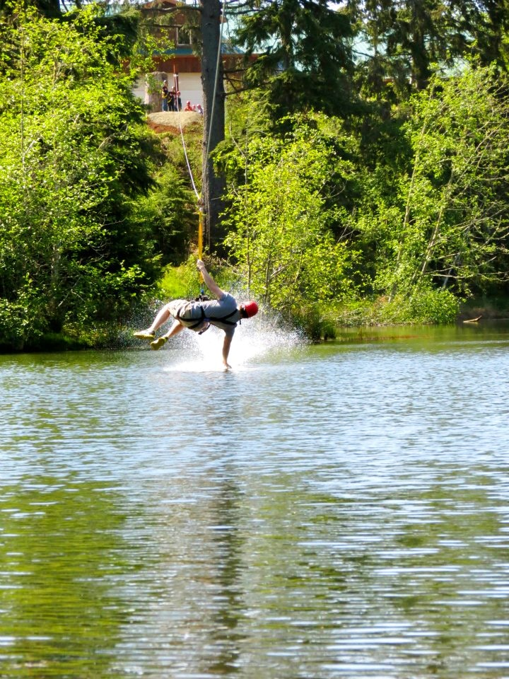 A zipliner skims the water on the Maple zipline