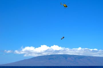 Maui emergency first response helicopter training with Lanai island in the background.