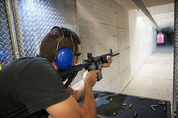 Man shooting rifle at indoor range