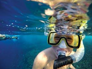 Kid wearing snorkel mask underwater near Molokini Crater in Maui