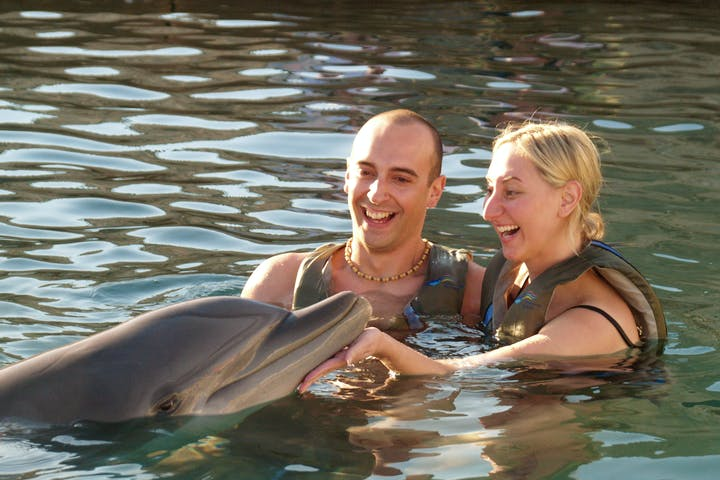 couple in water with dolphin