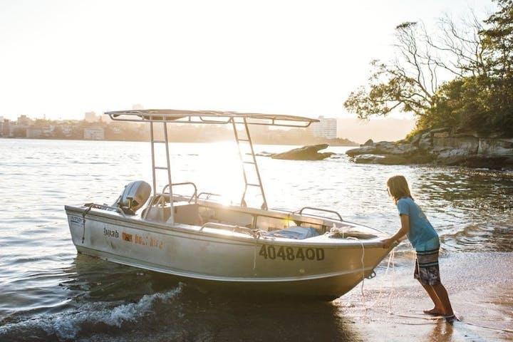 Guy pushing the boat near the shore