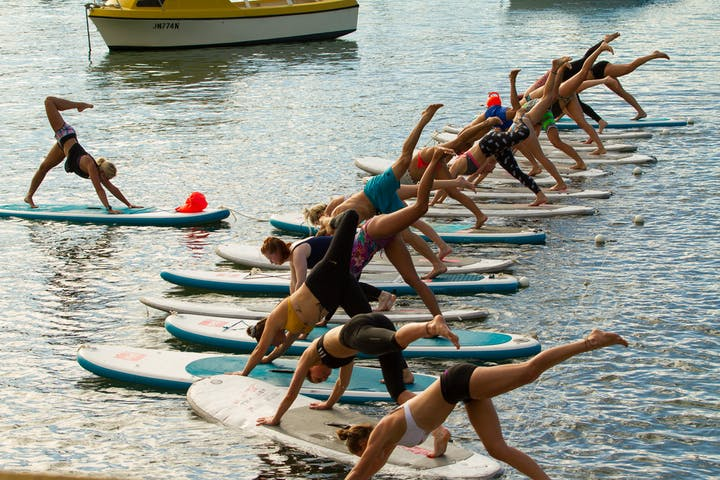 People doing SUP yoga pose on the beach