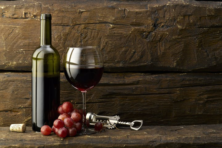 bottle of wine, wine glass, grapes & bottle opener