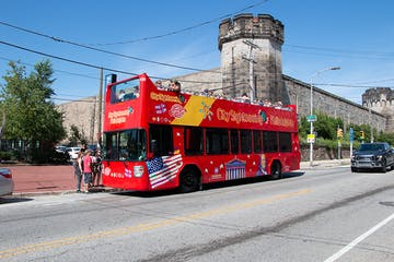 a red double decker bus parked on the side of a road
