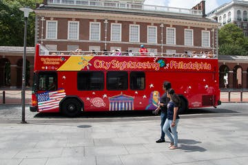 a red and white bus parked in front of a building