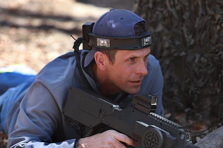 man lying prone with laser tag gun