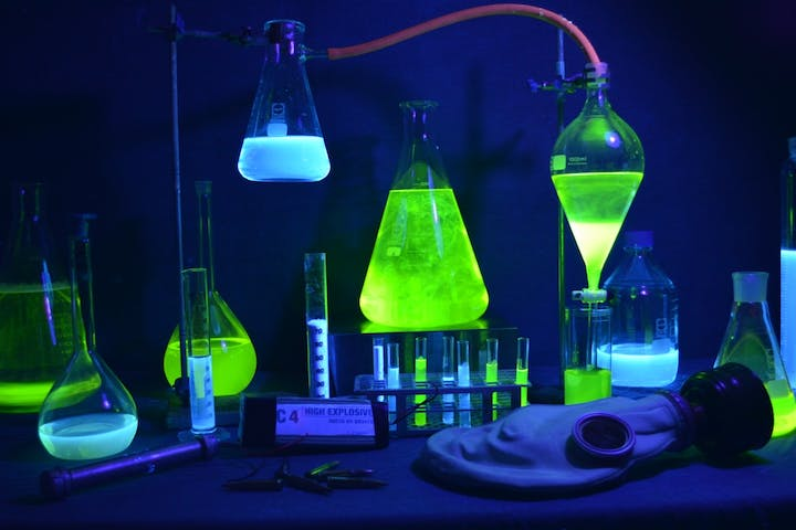 beakers with green and blue chemicals in them