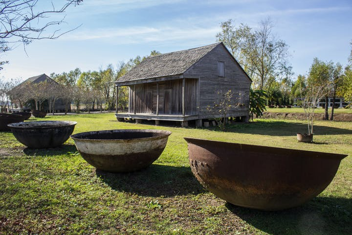 A few large bowls and an old cabin at the Whitney plantation during a whitney plantation tour