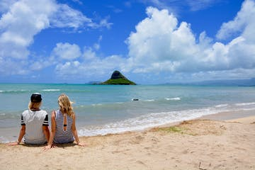 women sitting on beach in O'ahu