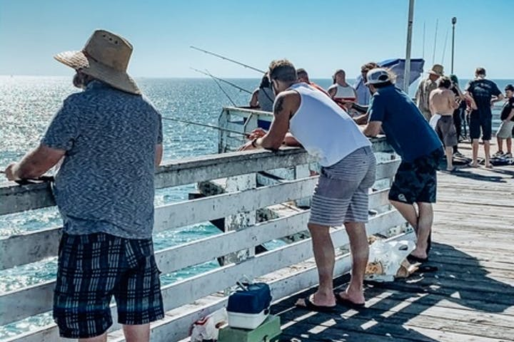 standing at the pier fishing