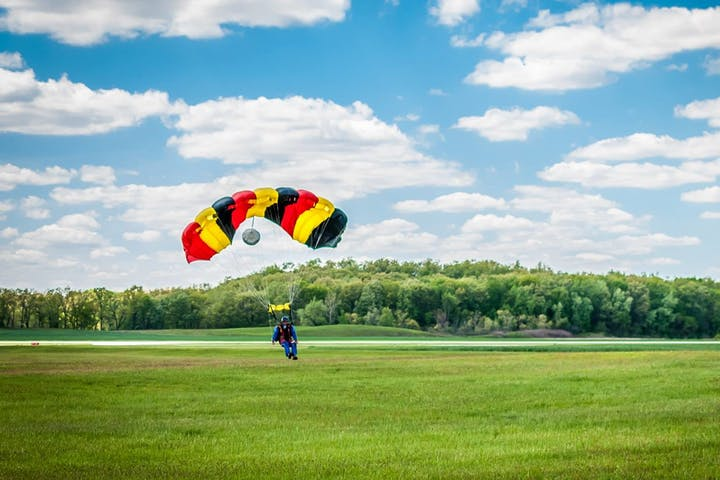 skydiver with parachute landing in a field