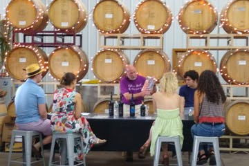 a group of people sitting at a table with wine tasting