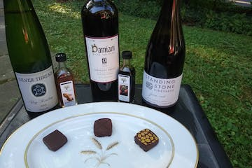 a close up of a plate of chocolates and bottles of wine