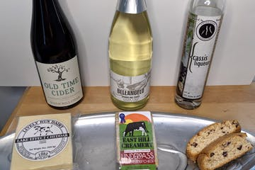 a bottle of wine, cider and liqueur with cheese and biscotti