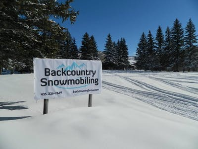Backcountry Snowmobiling sign in the snow