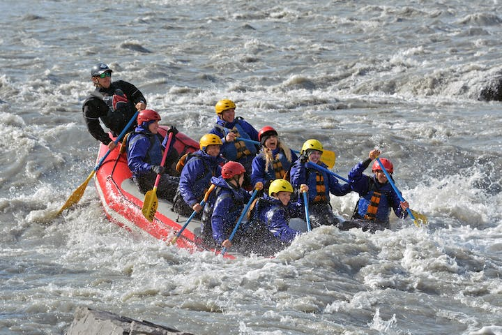 Friends rafting in wile raft with paddles