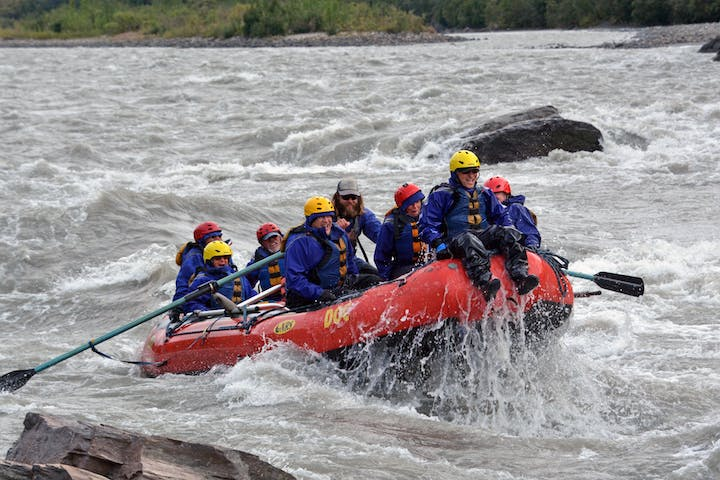 Friends rafting among rapids