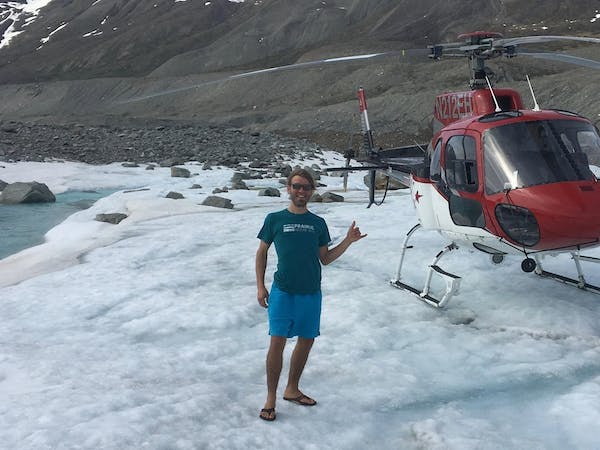 Pilot with helicopter on glacier