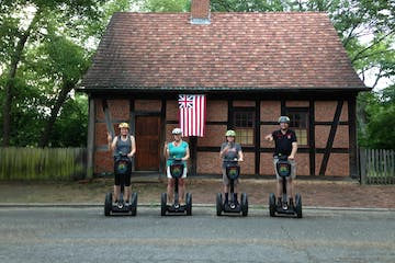People on Segway PTs in front of house