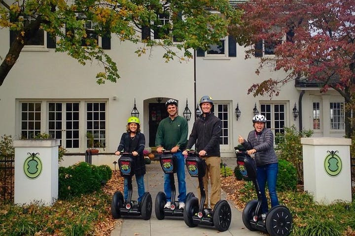 People on Segway PTs in front of a white house
