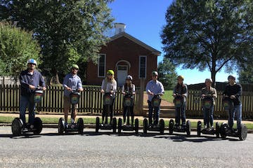 People on Segway PTs in front of a brick house