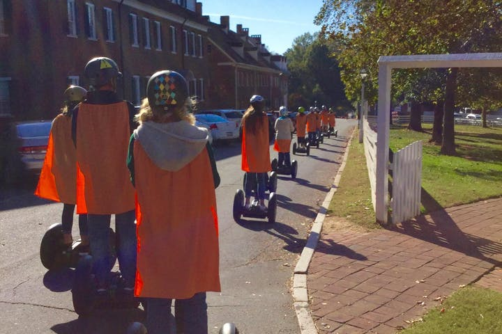 People on Segway PTs with orange capes