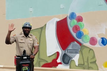 Sherif waving hi on a segway in front of a mural of a gumball machine losing its gumballs