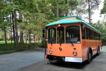 Orange Trolley with teal roof driving near a park