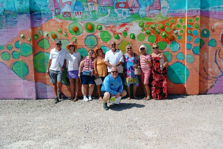 Group of older people in True Tours Fort Myers posing in front of colorful mural