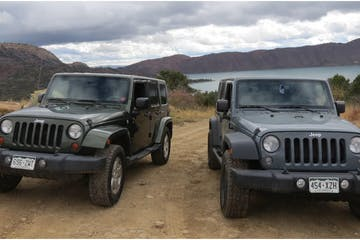 two Jeeps parked in the mountains